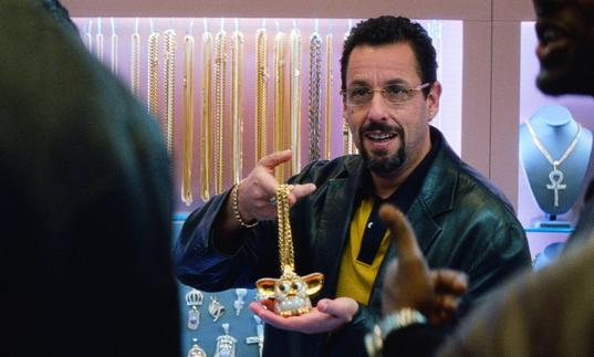 Adam Sandler as a jewellery dealer holding up a gold chain
