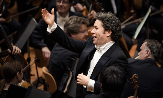 Gustavo smiling joyfully whilst conducting