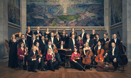 A portrait of the Norwegian Chamber Orchestra clutching their instruments