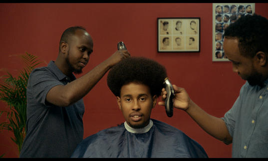a man sitting in the barber chair with two barbers cutting his hair