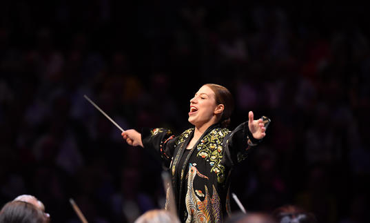 Dalia's arms outstretched as she conducts