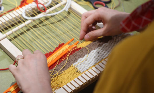 Woman using weave to make textile