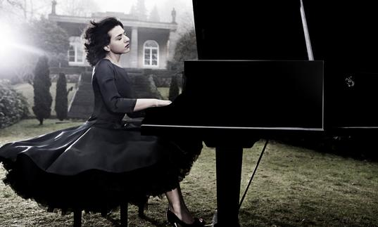 An ethereal image of Khatia in a stately garden with wind in her hair, expertly playing the piano with great emotion