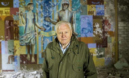 David Attenborough in front of a painted mural
