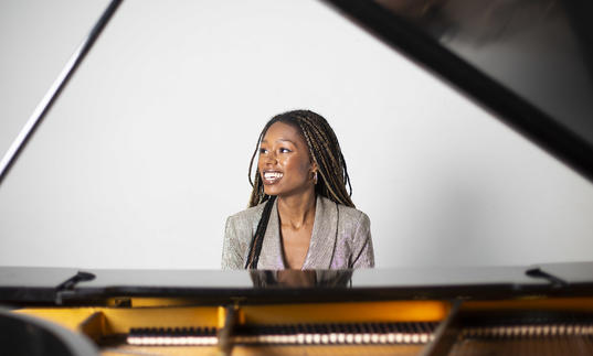 Am image of Isata sitting by the piano and smiling