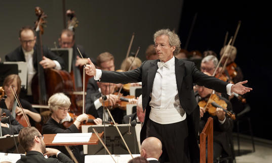 An image of Franz Welser-Möst conducting the Cleveland Orchestra with great enthusiasm
