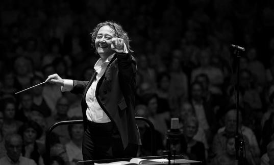 An image of Nathalie pointing at the camera joyfully whilst conducting in a recent concert