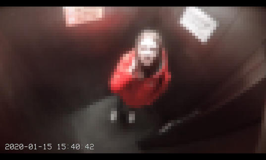 A pixelated view from a CCTV camera of someone looking up at the camera in a small room. They are wearing a red coat and they have brown hair.