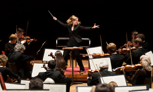 An image of Migra Gražintė-Tyla conducting the City of Birmingham Symphony Orchestra with great vigour