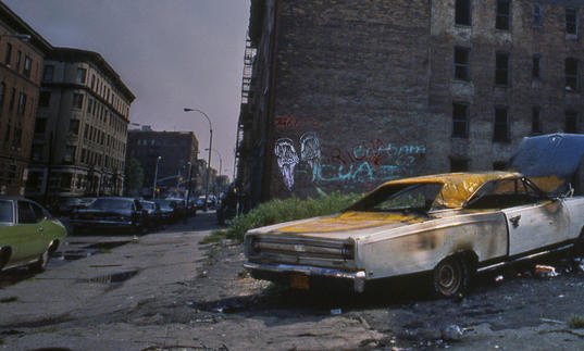 Shot of burnt out car on a bronx street corner