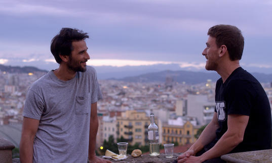 Two men gaze at each other with the violet-tinted cityscape of Barcelona as their backdrop