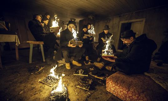 A group of people sit around in a dark room reading books that have flames emerging from the pages.