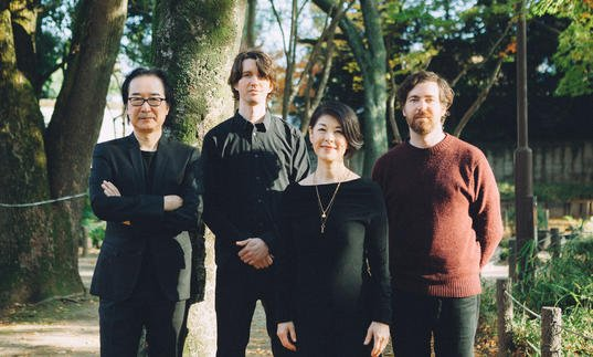 Spencer Doran and Ryan Carlile (Visible Cloaks) with Yoshio Ojima and Satsuki Shibano standing in a park