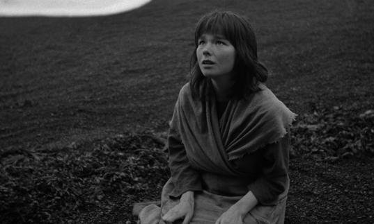 A black and white image of young Bjork kneeling on the ground looking up