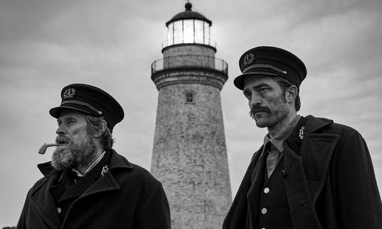 A black and white photo of Willem Dafoe and Robert Pattinson looking into the distance with a lighthouse behind them