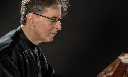 Robert Levin playing the piano, wearing a flowing black silk shirt