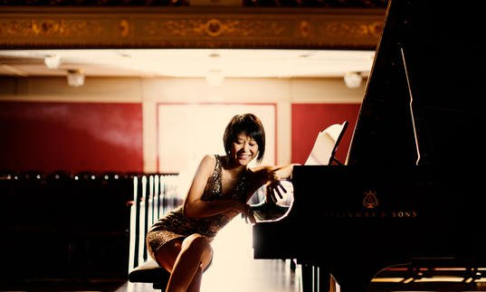 An playful image of Yuja sitting at her piano, facing the camera