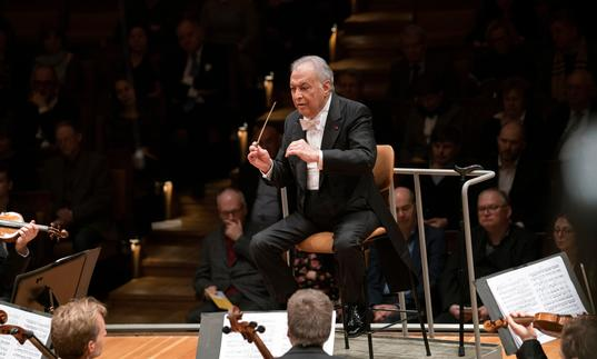 Zubin Mehta conducting the Berlin Philharmonic from a chair