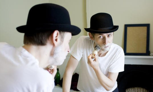 Colour photo of Neil Hannon wearing a bowler hat, shaving with foam on his face