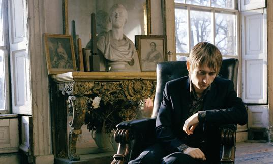 A colour photo of Neil Hannon lounging in a chair in a slightly dilapidated stately home, with antique furniture in the background
