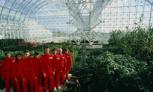A large group of people dressed in red jumpsuits stand inside a large glass biodome, with plants