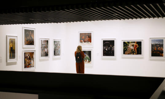 Woman looking at a wall filled with photographs