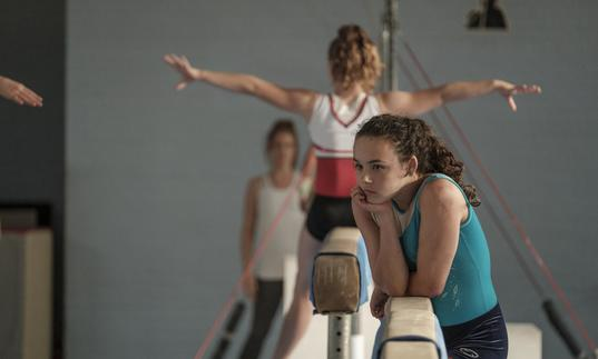 teenage girl looks wistful leaning on a balancing bar in a gymnastics hall