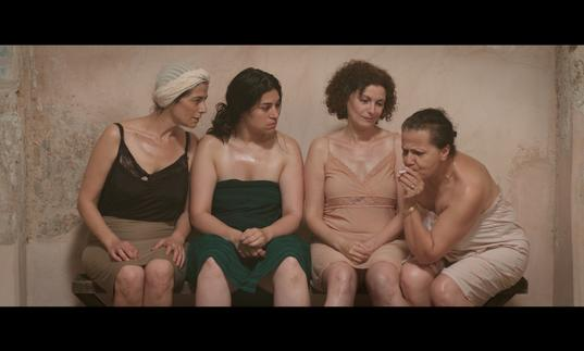 a group of women are in a bathing house together, talking