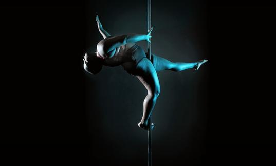 a fat black dances on a pole in darkness, lit by a blue light