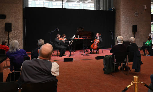 Audiences enjoying a socially distanced performance by the Mithras Trio on Barbican Level G