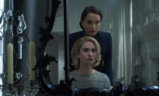 Lily James (playing Rebecca) looking into a mirror with Kristen Scott Thomas standing over her