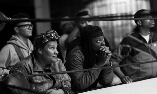 Radha Blank sits at the side of a boxing ring