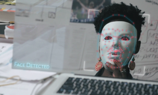 In front of a computer, a black woman holds up a white AI mask being detected by a computer, in Coded Bias