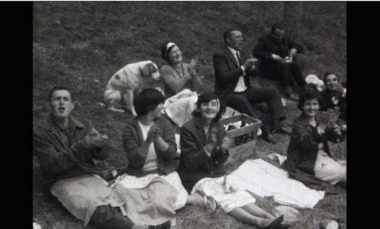 a black and white image of a group of people having a picnic