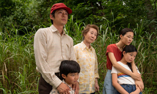 a family stand together with green landscape behind them