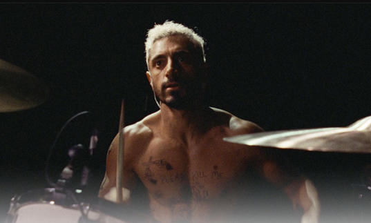 a drummer with bleached blonde hair and no shirt