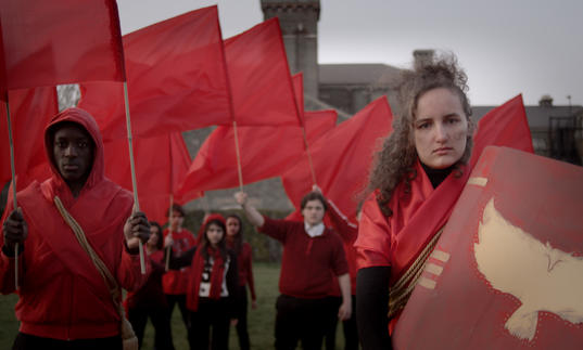 A group wearing red clothes and waving red flags