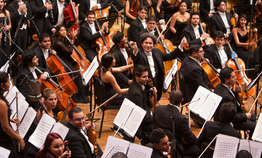 A full colour photograph of Gustavo Dudamel and the Los Angeles Philharmonic
