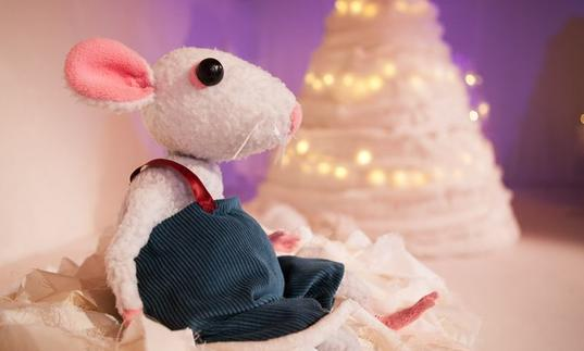 A photo of a mouse puppet against a snowy background