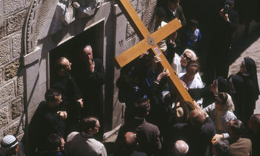 Photo of large cross being carried during performance of St John Passion