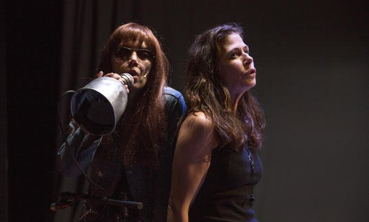 Image shows two women with long hair leaning against each other and singing