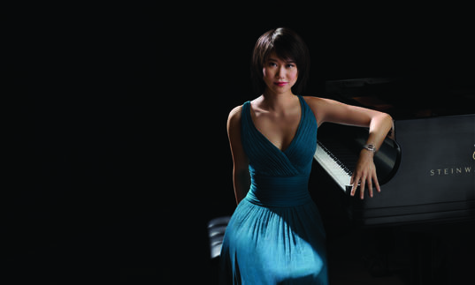 A colour photograph of Yuja Wang by a piano